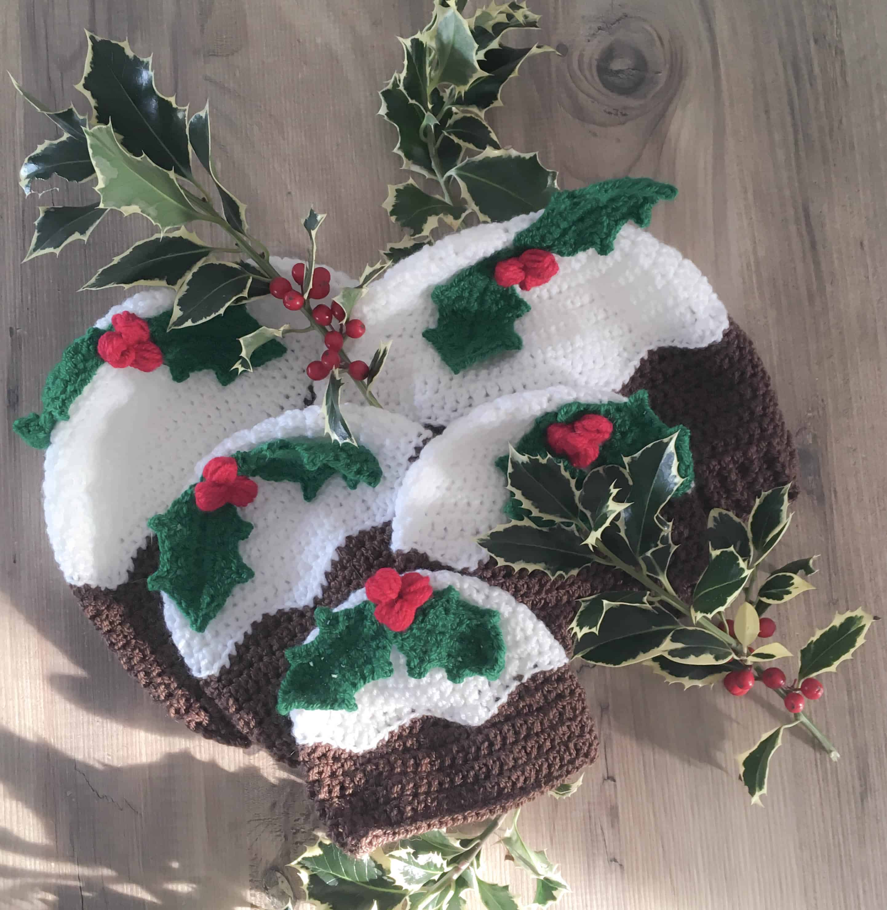 multiple sizes of crochet christmas pudding hats with holly leaf and berries