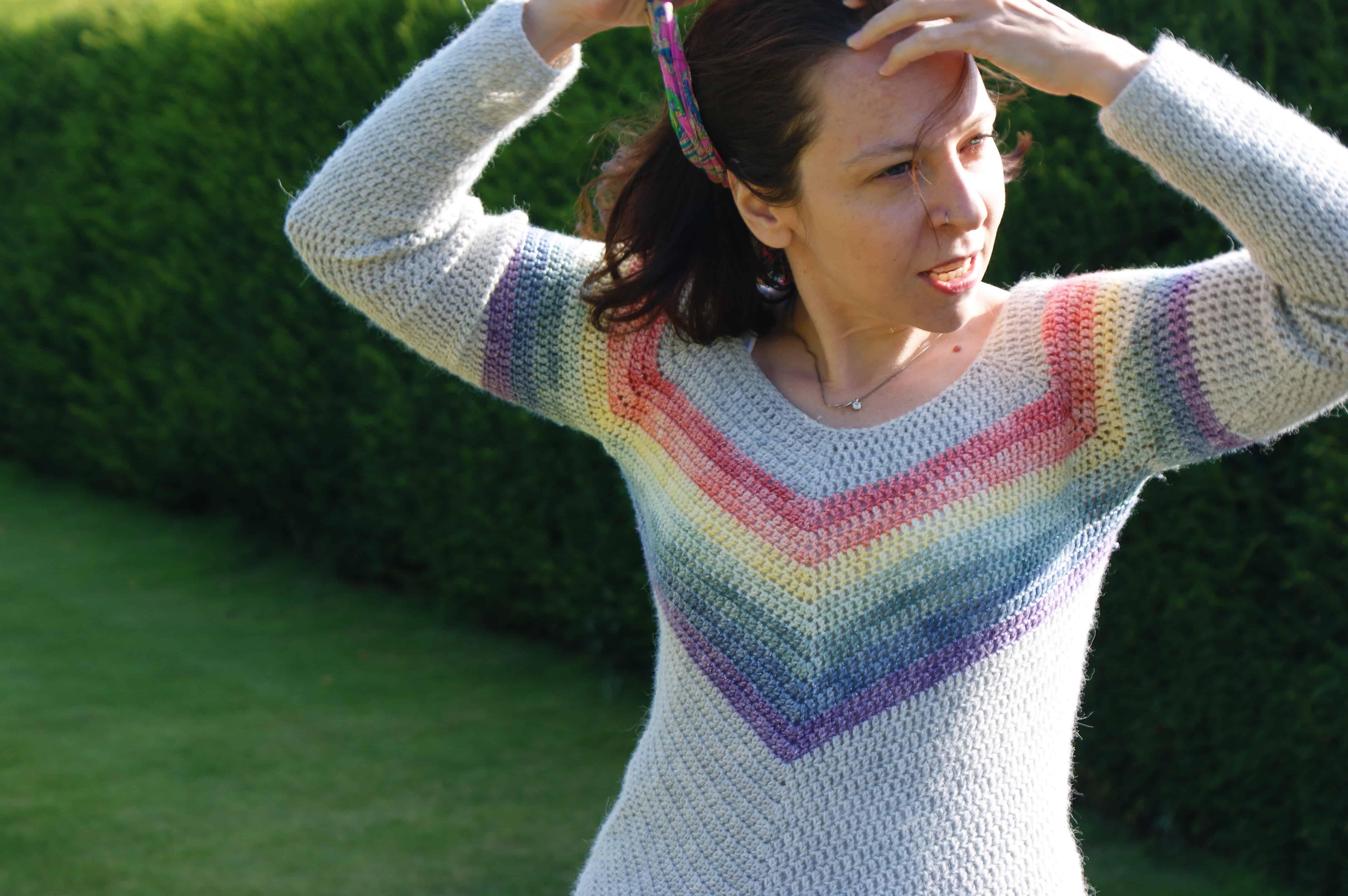 Woman in rainbow chevron crochet sweater in country garden