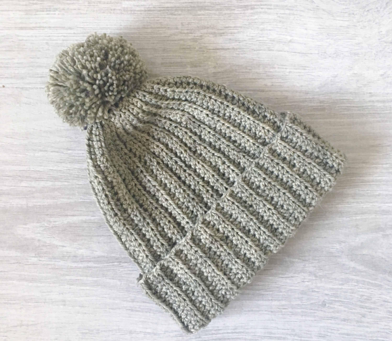 Olive green ribbed crochet beanie hat with pom pom on grey wood backgorund