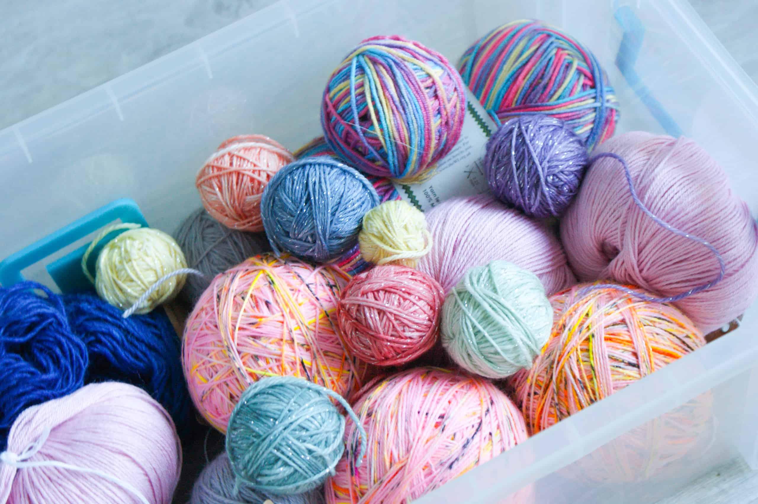 Multi coloured balls of yarn in a plastic storage box