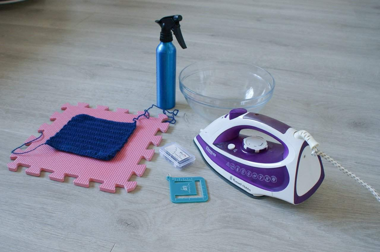A collection of materials ready to block a crochet swatch including an iron, water bowl, water spray, blocking board, pins, swatch measure and a swatch